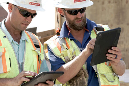 construction workers looking at drawings on an iPad