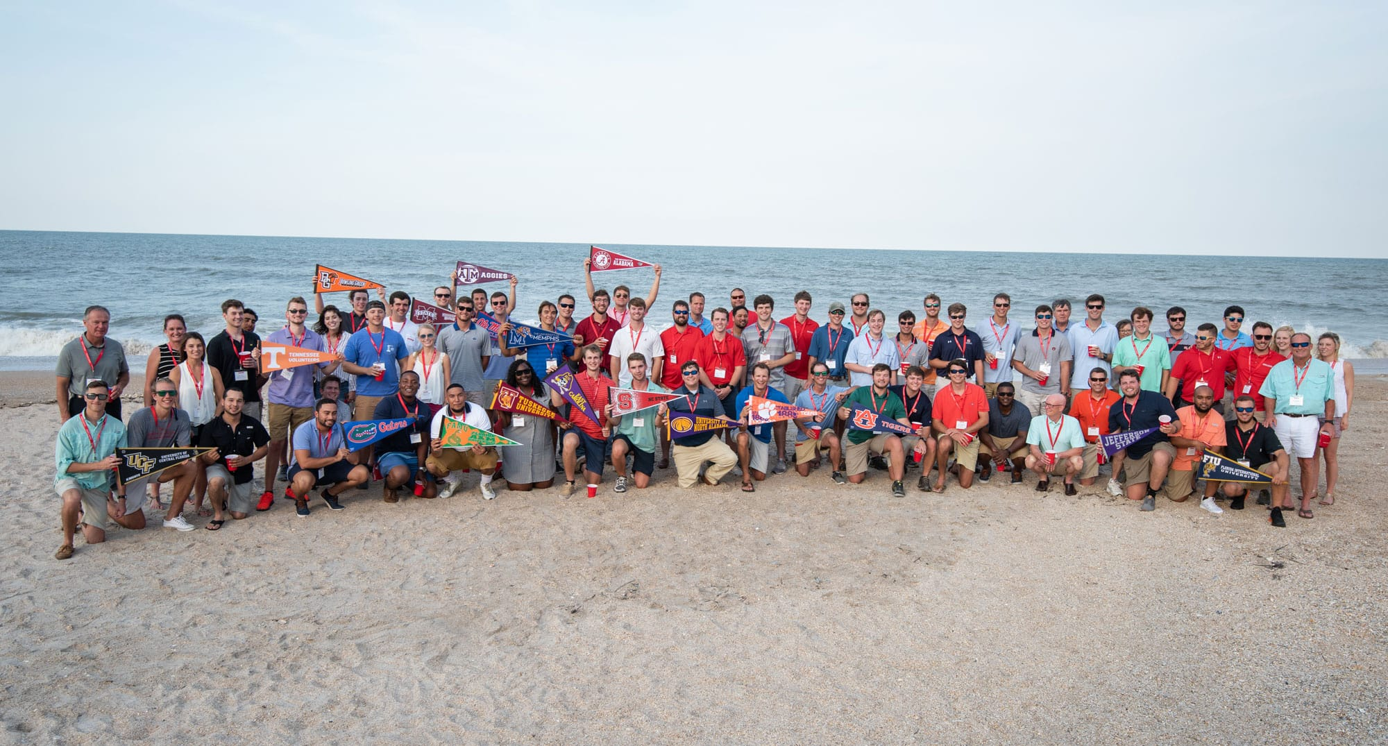 interns and staff at the beach holding college flags