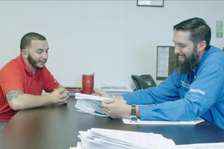 men discussing paperwork