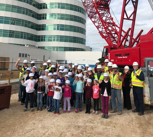 staff and children in front of a crane