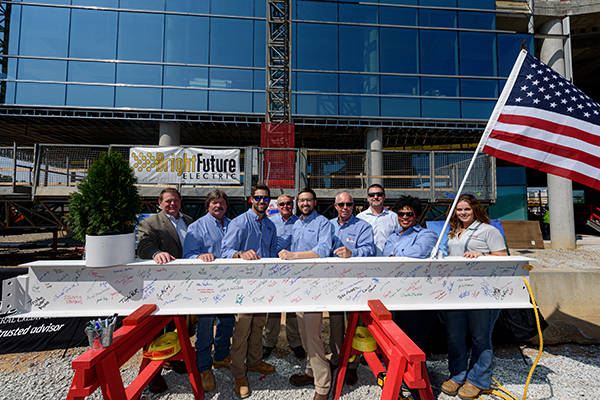 construction workers stand with beam