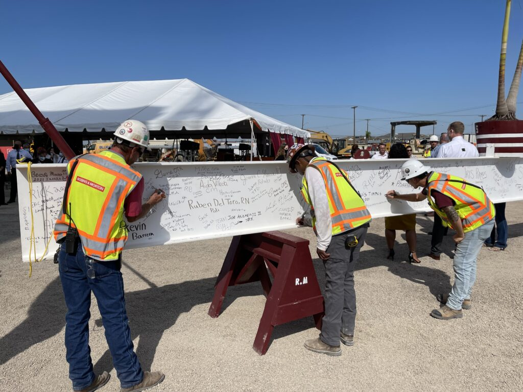 construction workers signing a beam