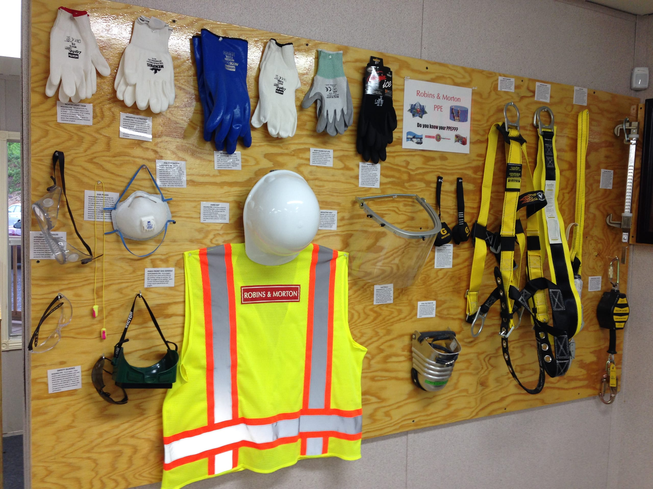 collection of safety equipment posted on a wood panel