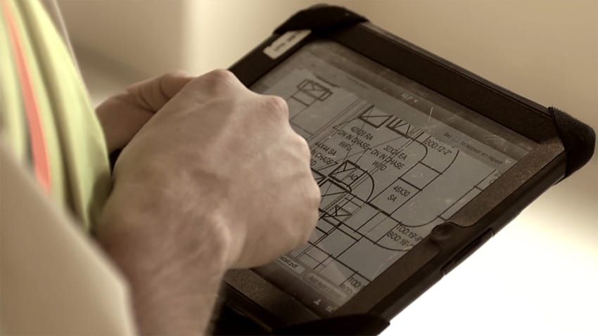 man using tablet with construction design software